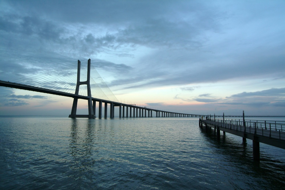 Links eine Brücke über das Wasser, rechts daneben ist ein Steg im Abendämmerung.
